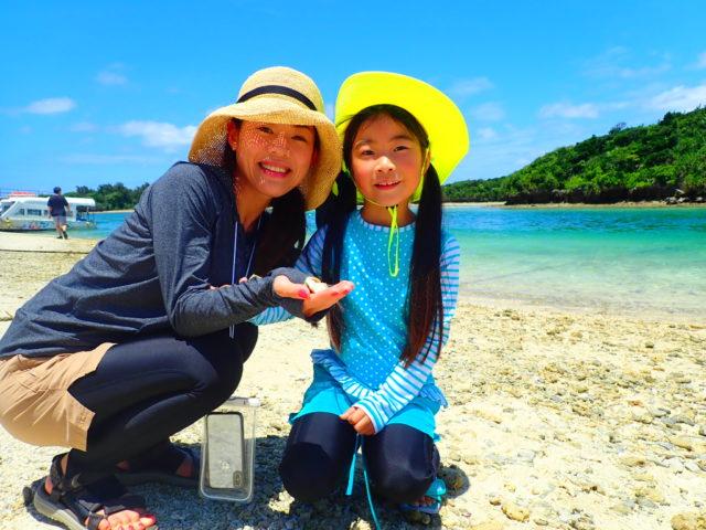 川平湾の海辺で貝殻を拾う親子 画像