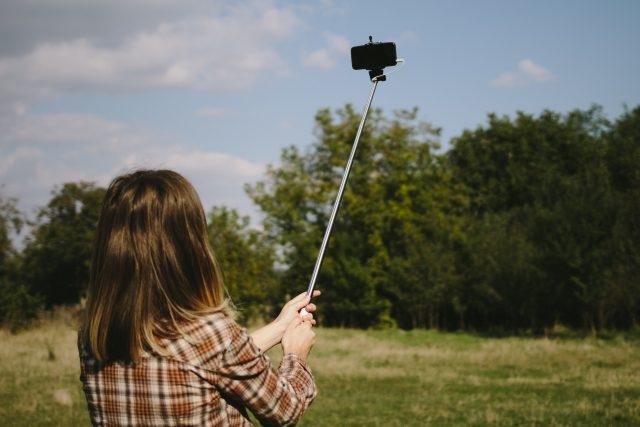 セルカ棒で自撮りをする女性の画像